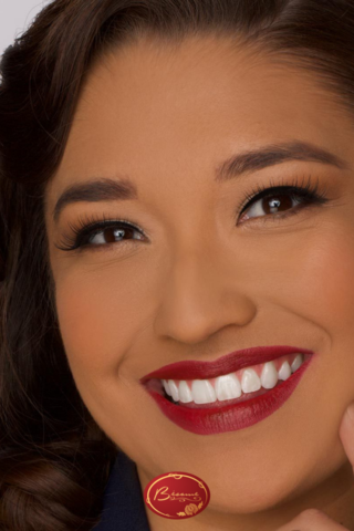 Woman smiling wearing Bésame Cosmetics Red Lipstick and Cake Mascara