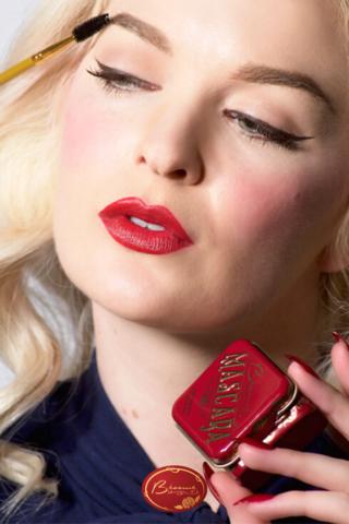 Woman Wearing Red Lipstick Applying Cake Mascara