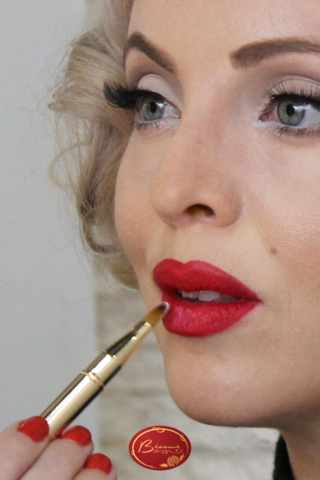 Woman-applying-Marylin-Monroe-red lipstick-with-brush